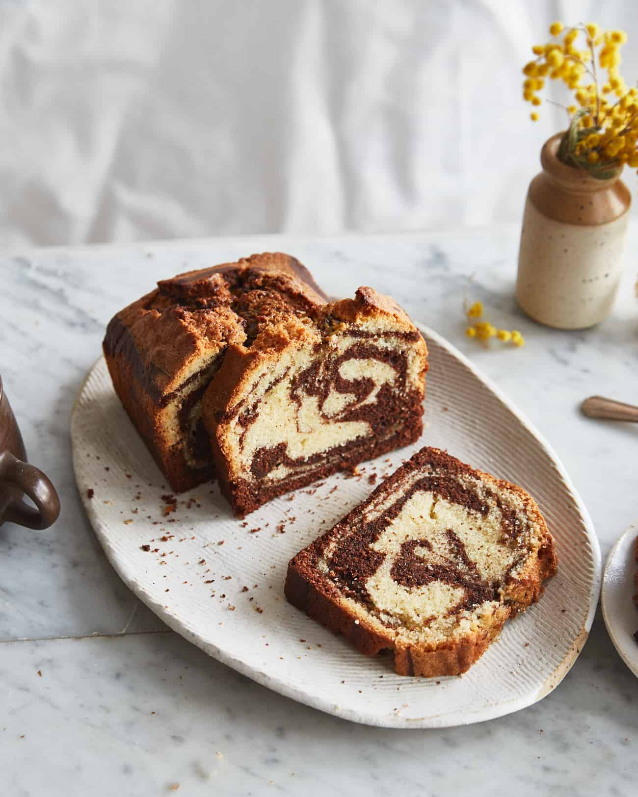 sliced marble cake on a plate with a vase
