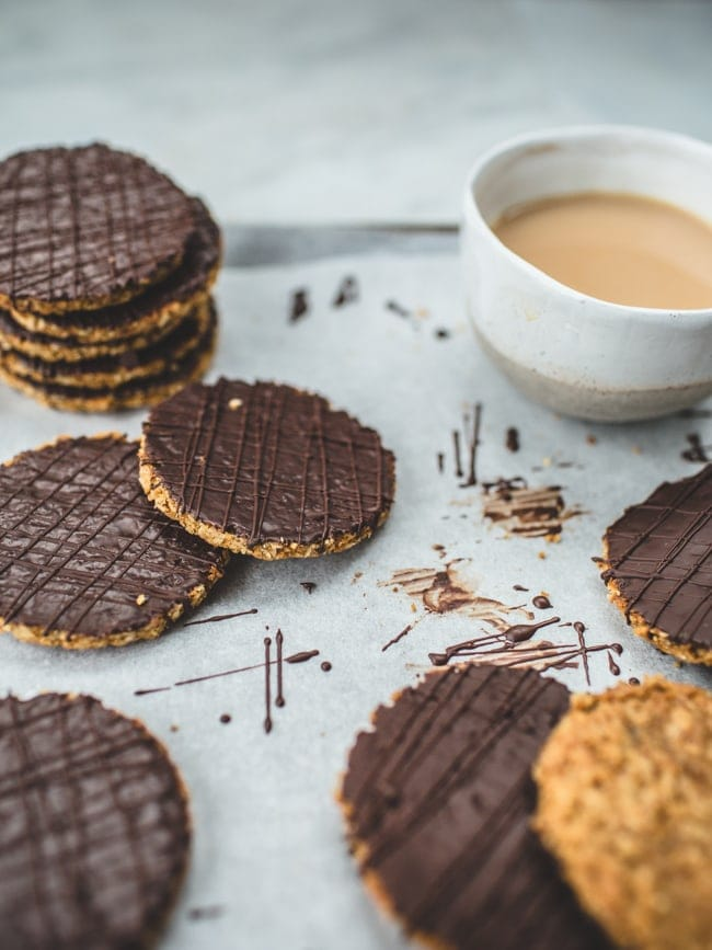 An array of homemade chocolate hobnob biscuits with a cup of tea