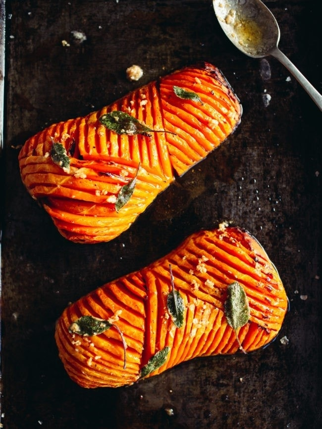 a baking tray with halved roasted butternut squash with decorative slits cut covered with garlic sage butter
