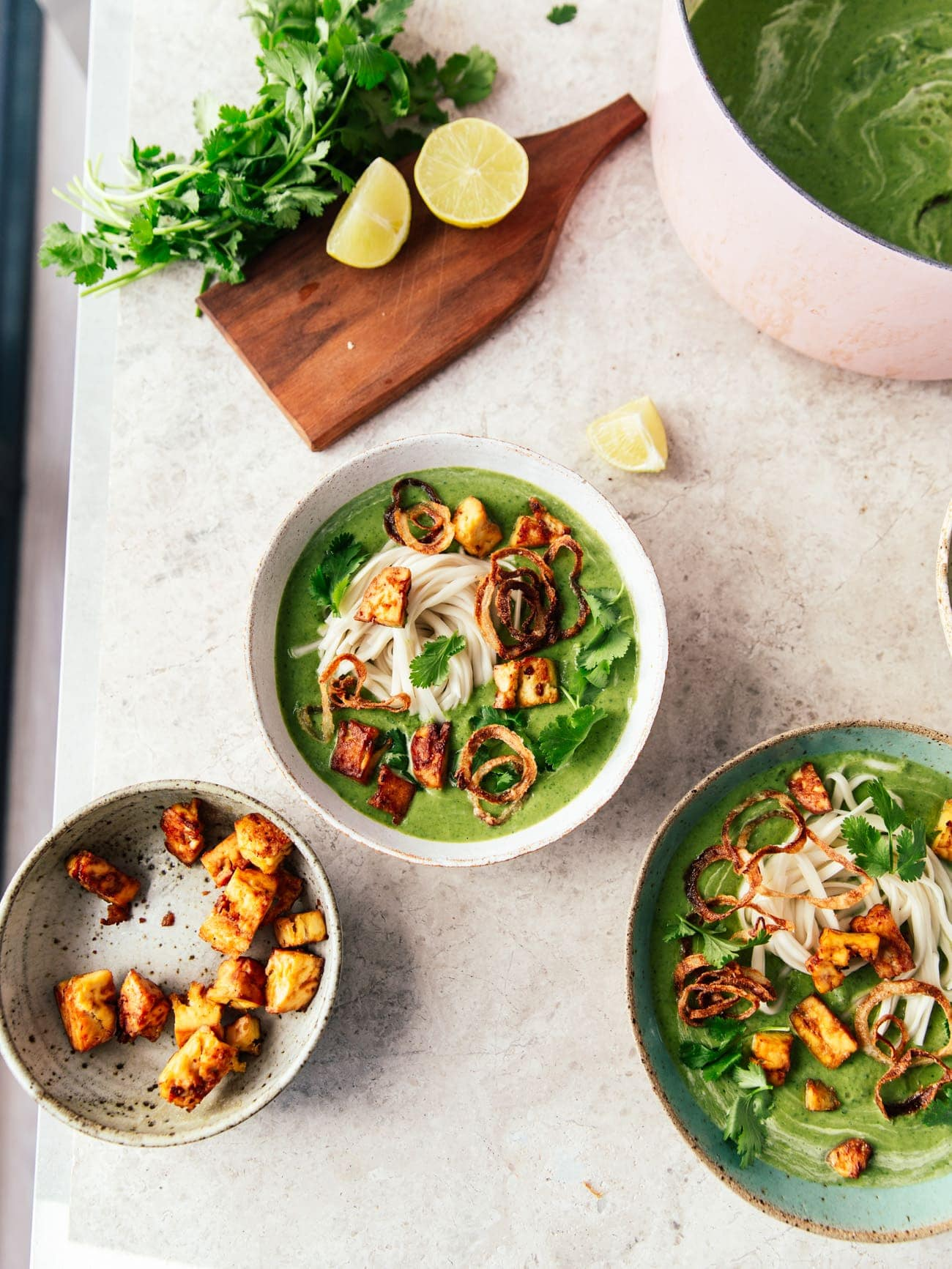 Two bowls and a pot of broccoli soup with smoked tofu, noodles, crispy onions and coriander by Izy Hossack