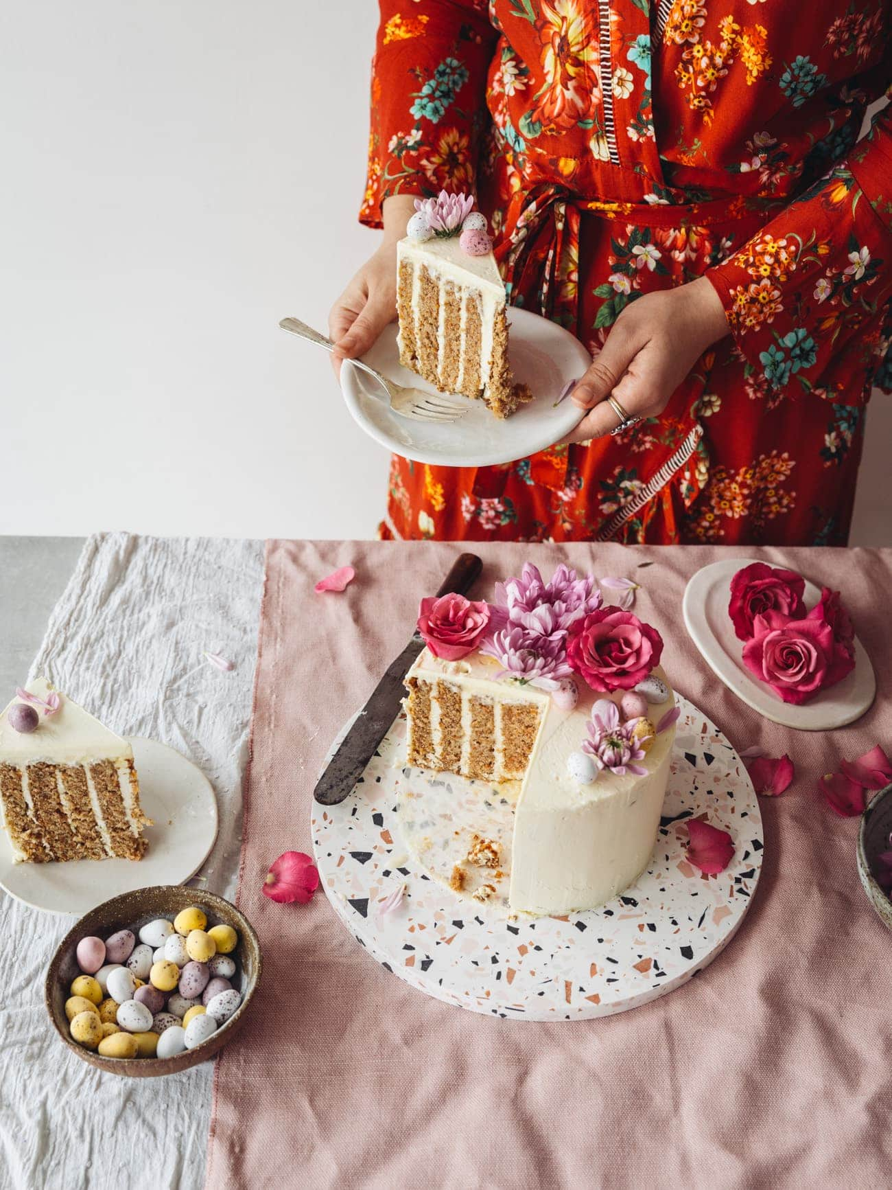 Holding a slice of Vertical Layer Carrot Cake with vanilla Swiss Meringue Buttercream by Izy Hossack