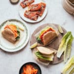 Bao buns filled with crispy gochujang tofu and lettuce with a bamboo steamer