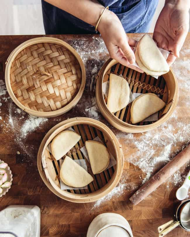 placing shaped bao buns into a bamboo steamer