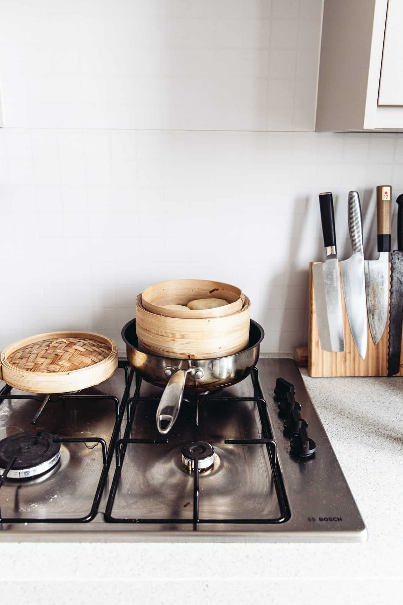 A bamboo steamer with bao buns in a pan on the stove