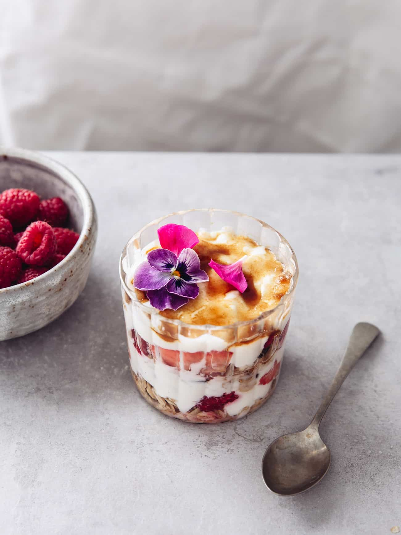 A glass with layers of yoghurt brulee, fruit and granola