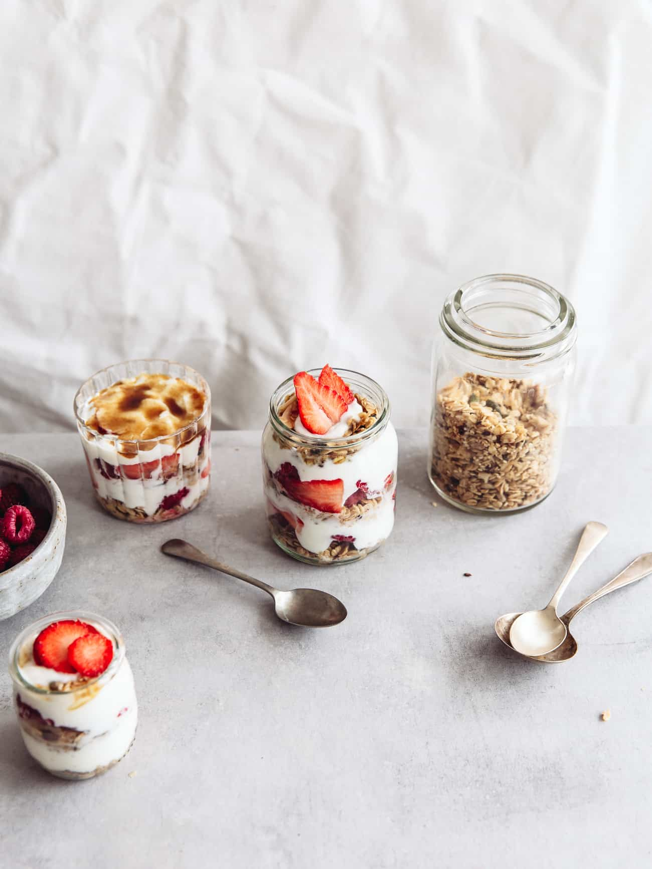 Three layered yoghurt brulees with berries and a jar of granola