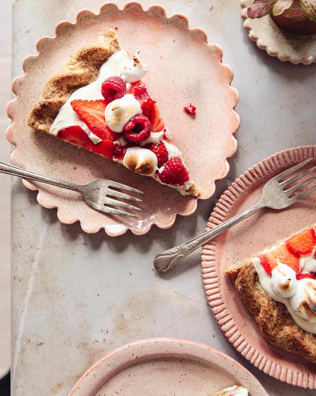 A slice of Eton mess tart on a pink scalloped plate