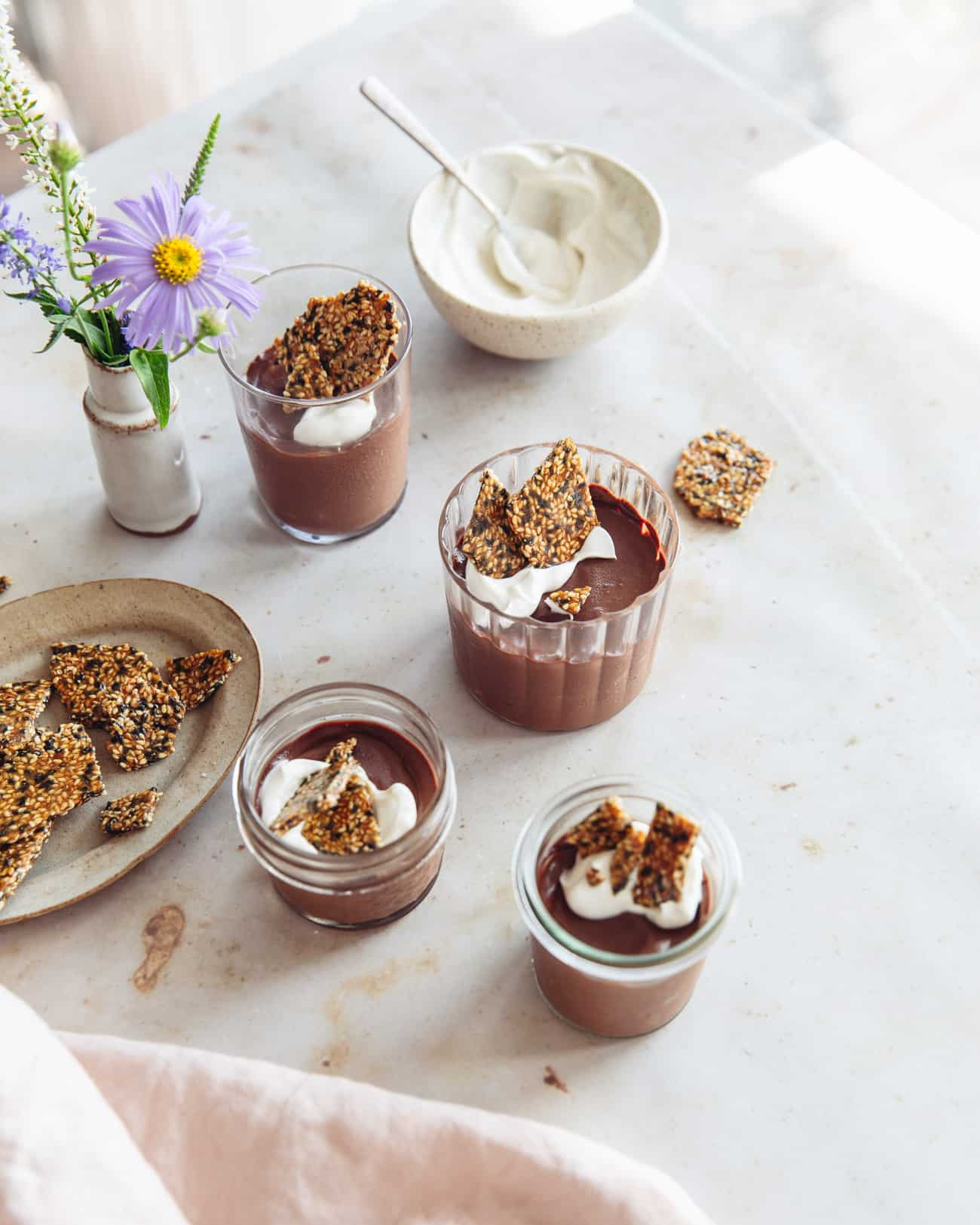 a cluster of glasses of chocolate tahini mousse with a bowl of creme friache, sesame brittle and a vase of flowers
