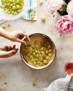 Hands adding gooseberries to an unbaked brown butter tart