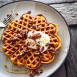 a plate with a pumpkin spice waffle and yoghurt and pecans on top