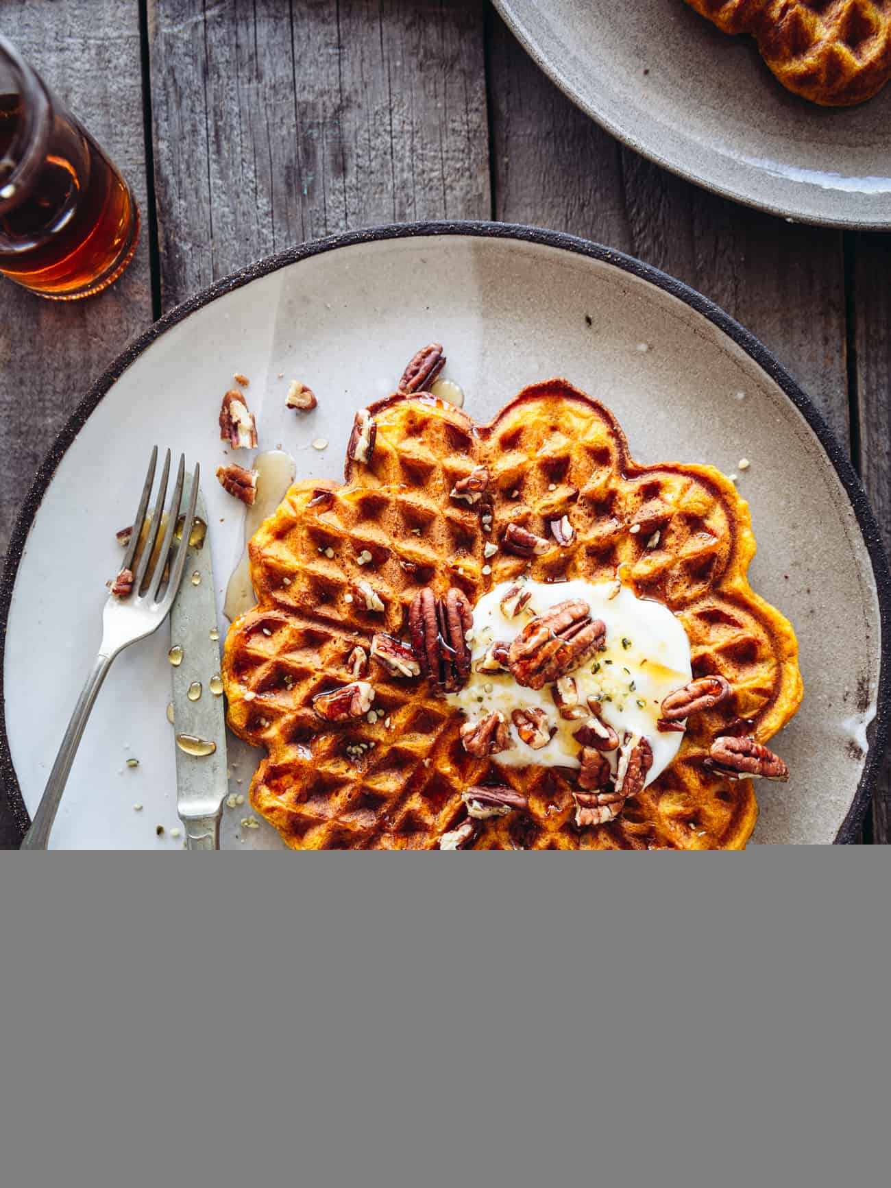 pumpkin spice waffles overhead on a table with maple syrup and pecans