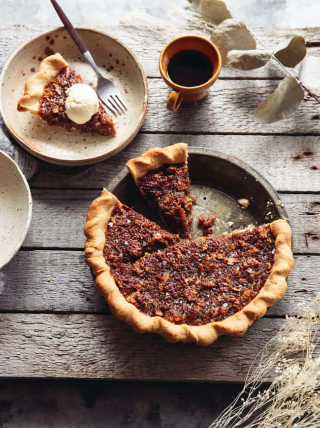 pie tin with vegan maple pecan pie and a slice taken out
