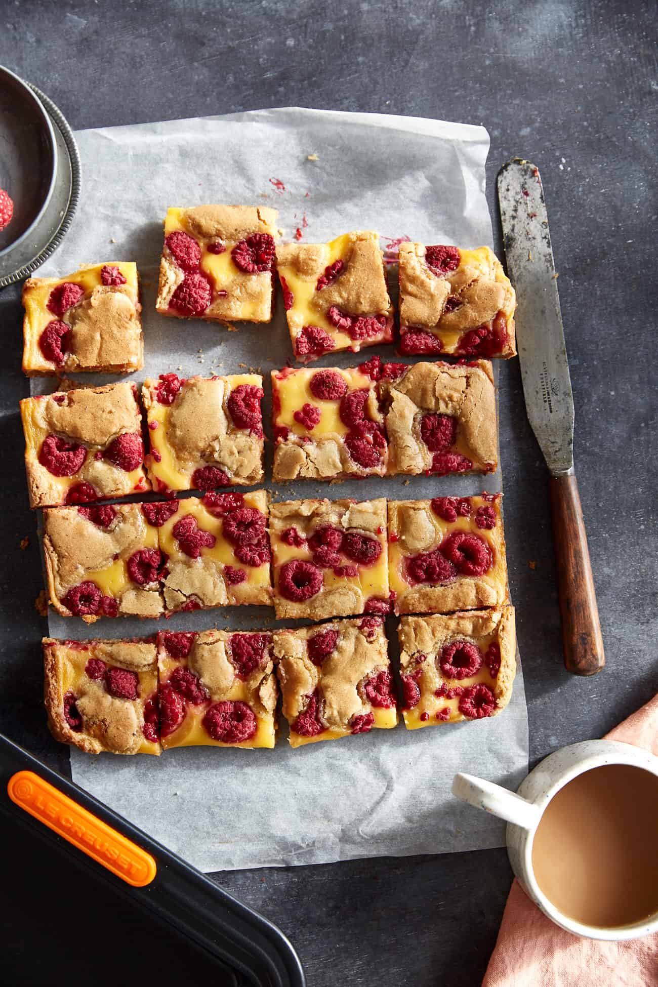 cut raspberry and custard blondies on a dark background with a cup of tea