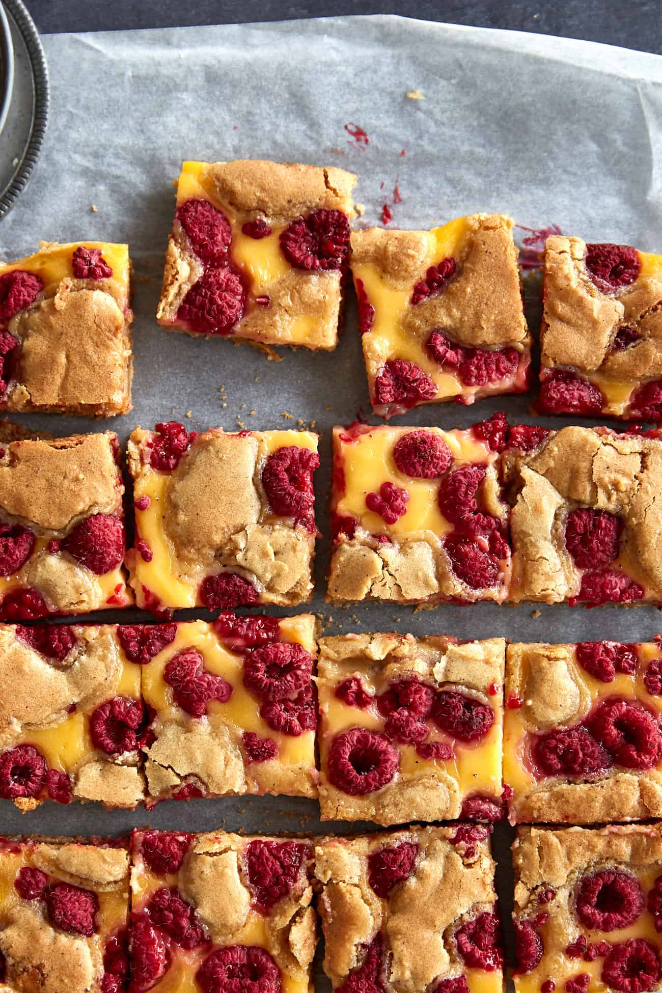 close up of raspberry custard blondies on baking paper