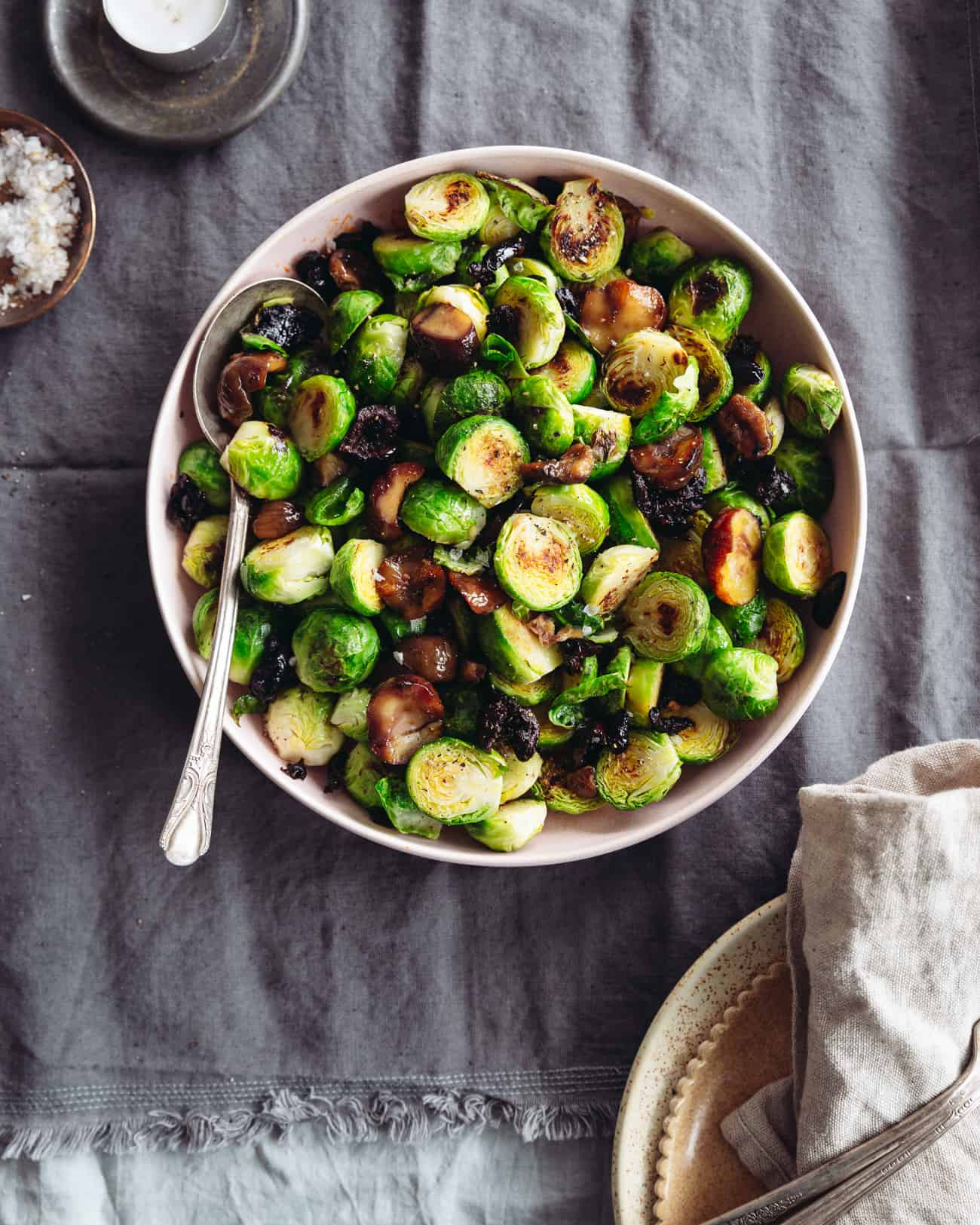A bowl of roasted Brussels sprouts with chestnuts and smoky olives on a table