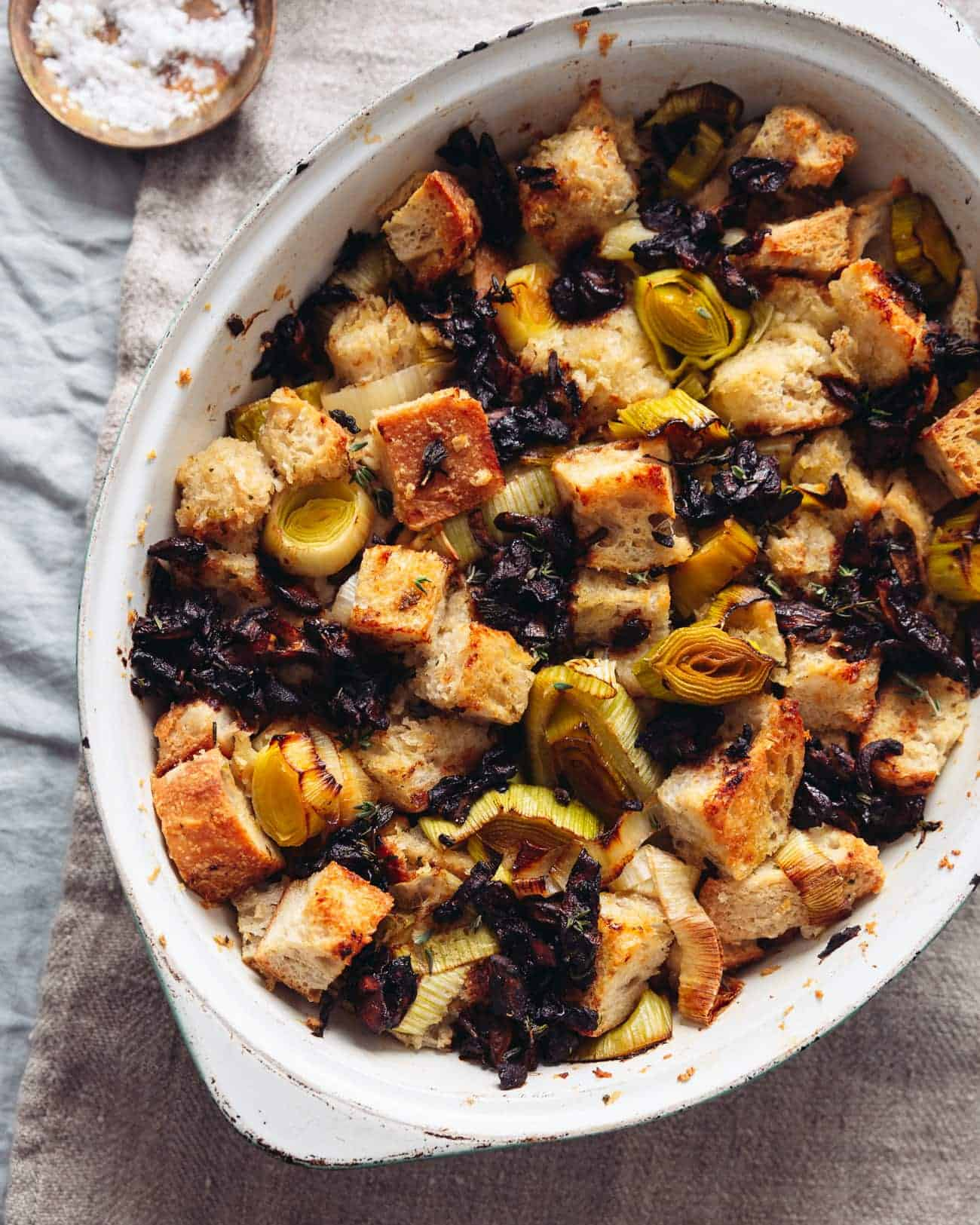 A close up of a dish of vegan sourdough stuffing with leeks and soy-sauce mushrooms