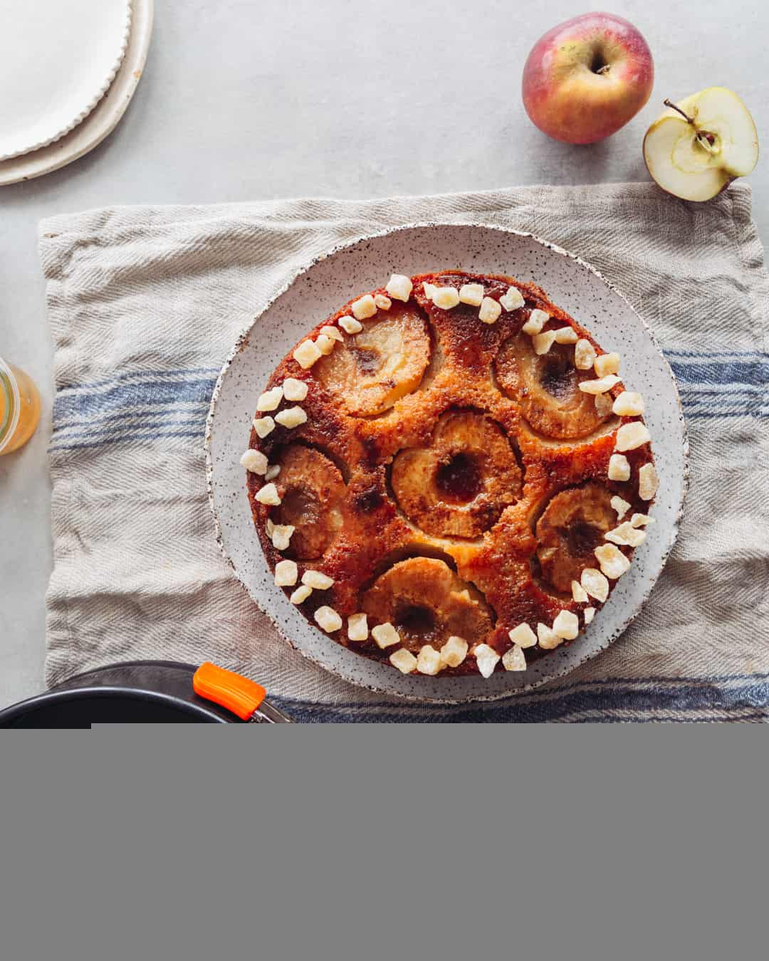 an upside-down apple and ginger cake overhead with mugs of coffee and a striped napkin