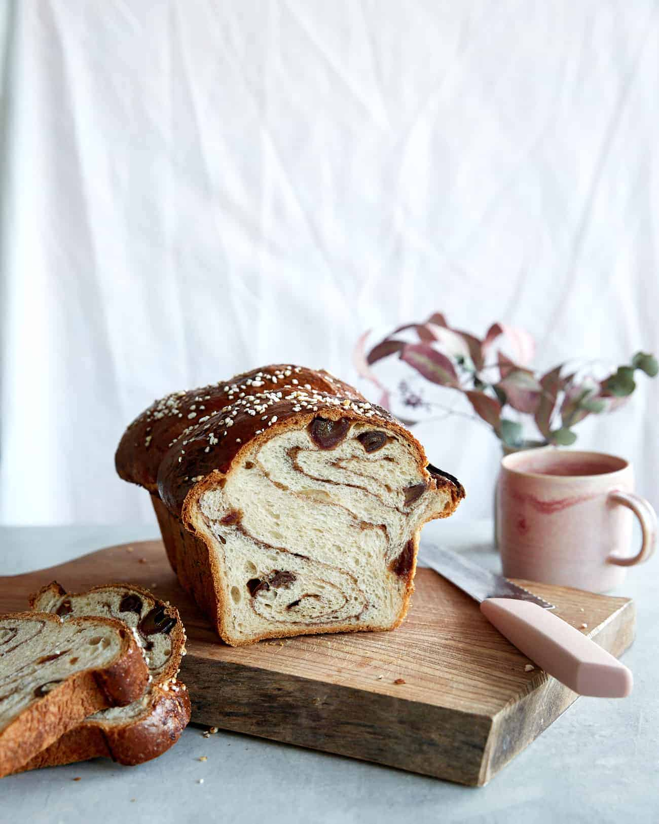 A cinnamon swirled sourdough loaf with a mug of tea on a chopping board