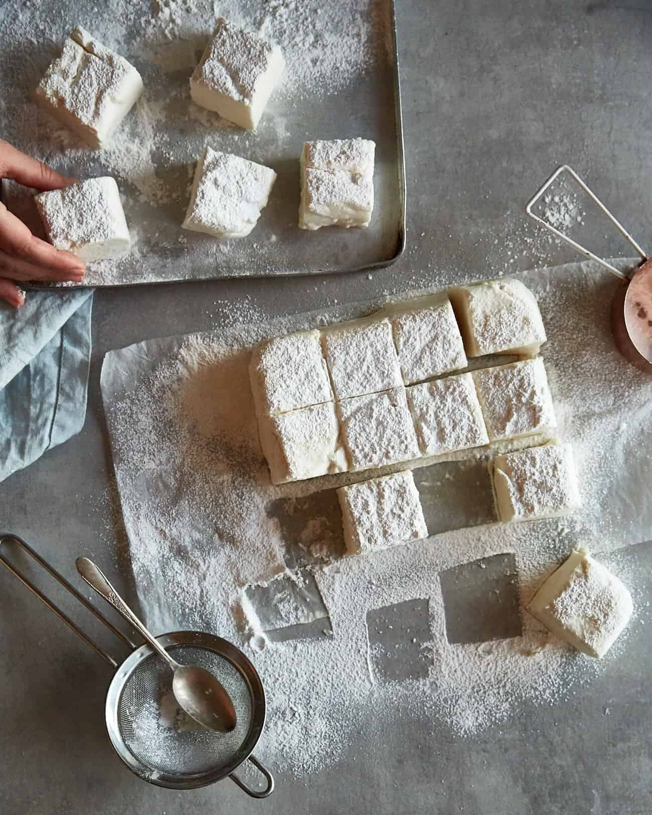 some cut vegan marshmallows on a worktop and on a baking sheet