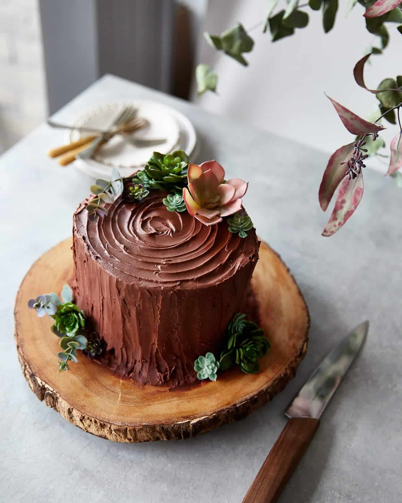a chocolate tree stump cake on a wooden cake stand