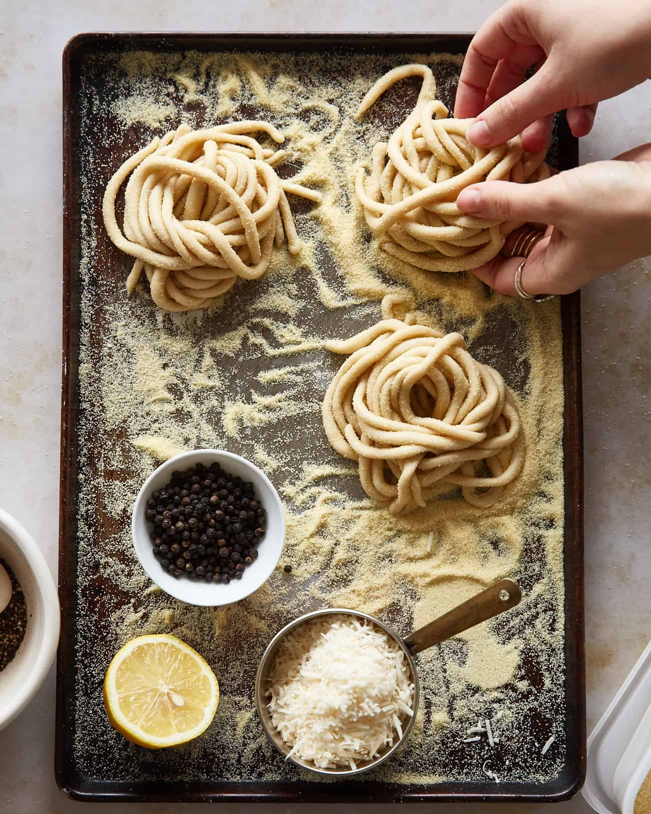 nests of pici dough on a tray with ingredients for cacio e pepe