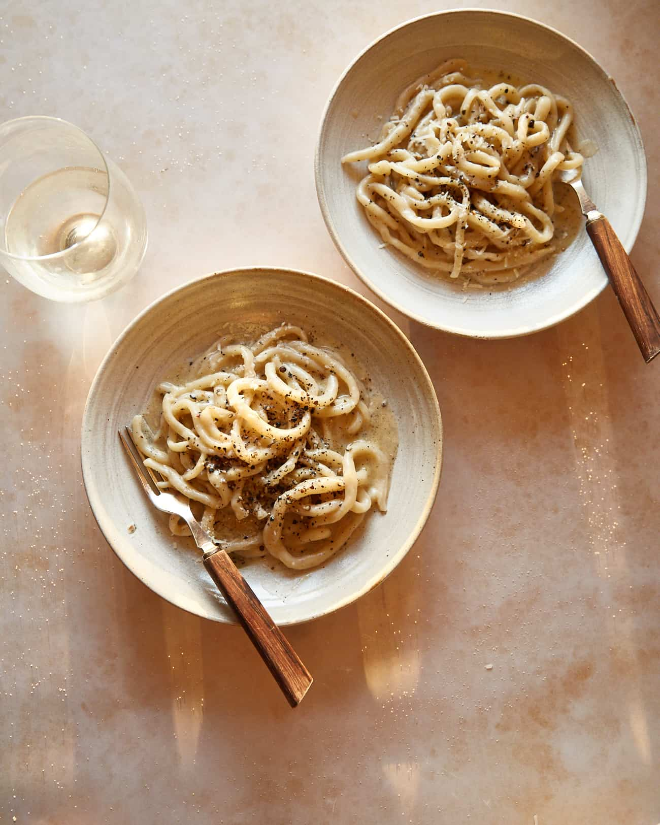 pici cacio e pepe in two bowls with a glass of wine