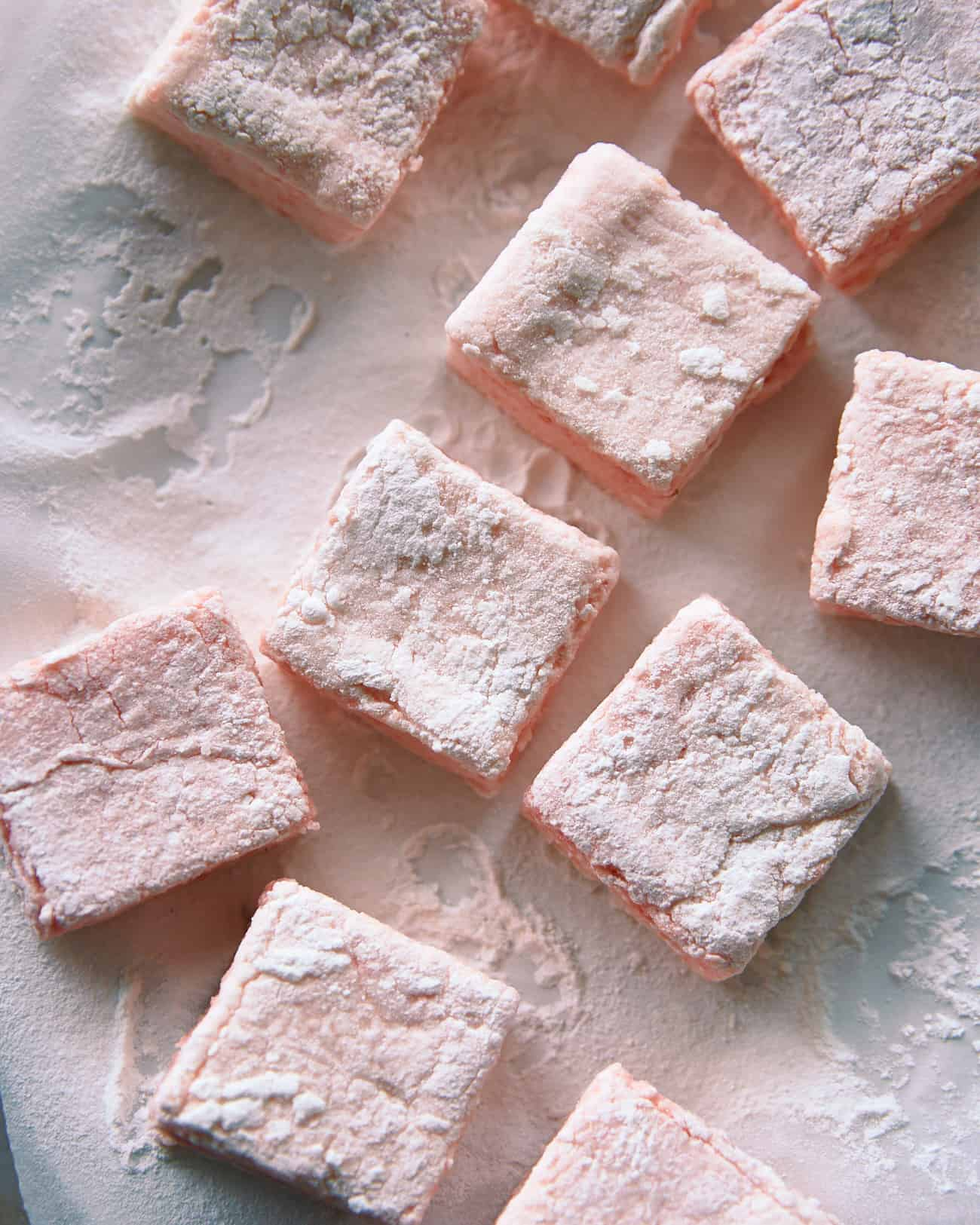 close up of vegan rhubarb marshmallows on baking paper, dusted with icing sugar