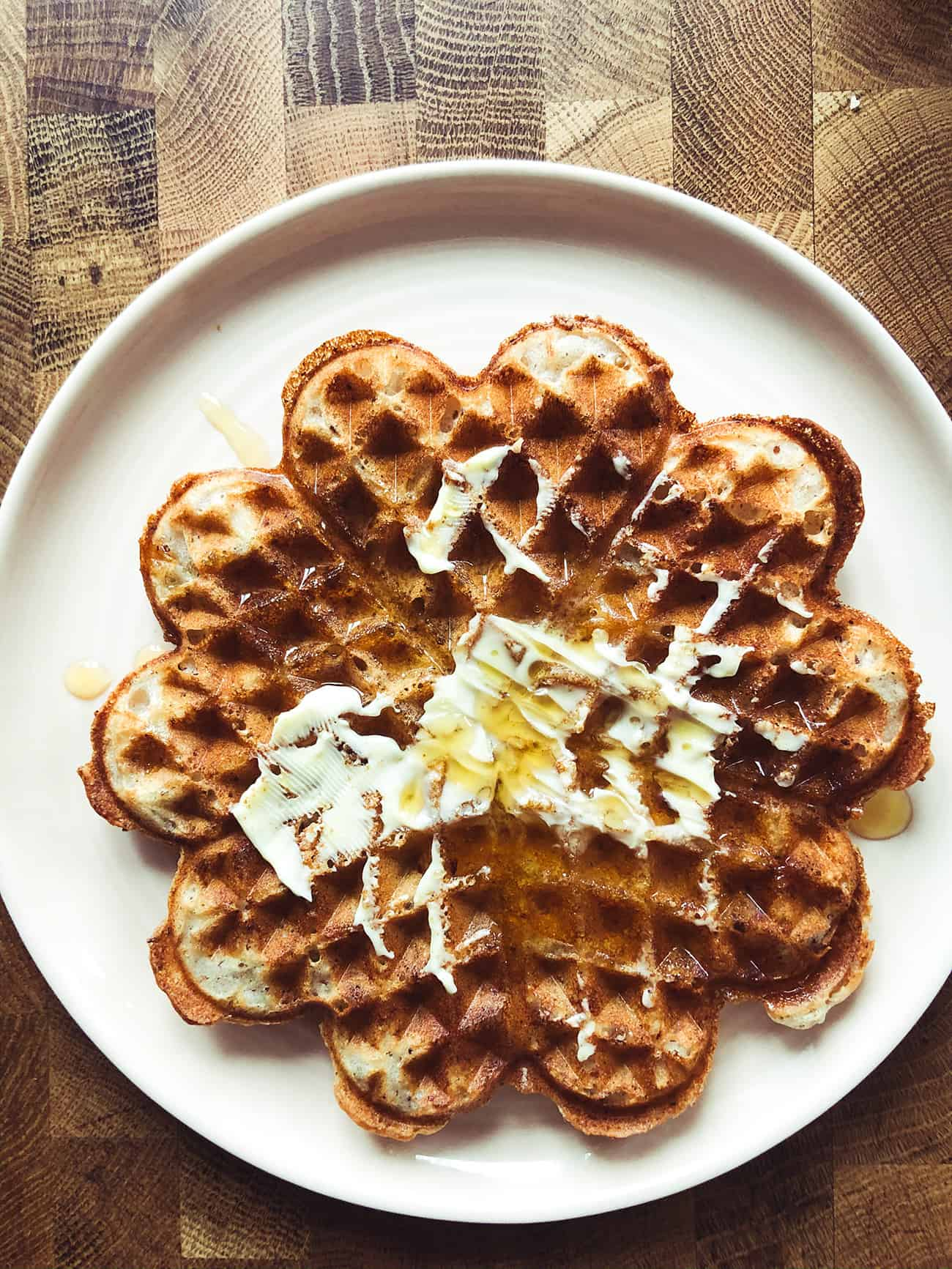 a crispy vegan waffle with butter and maple syrup on a plate