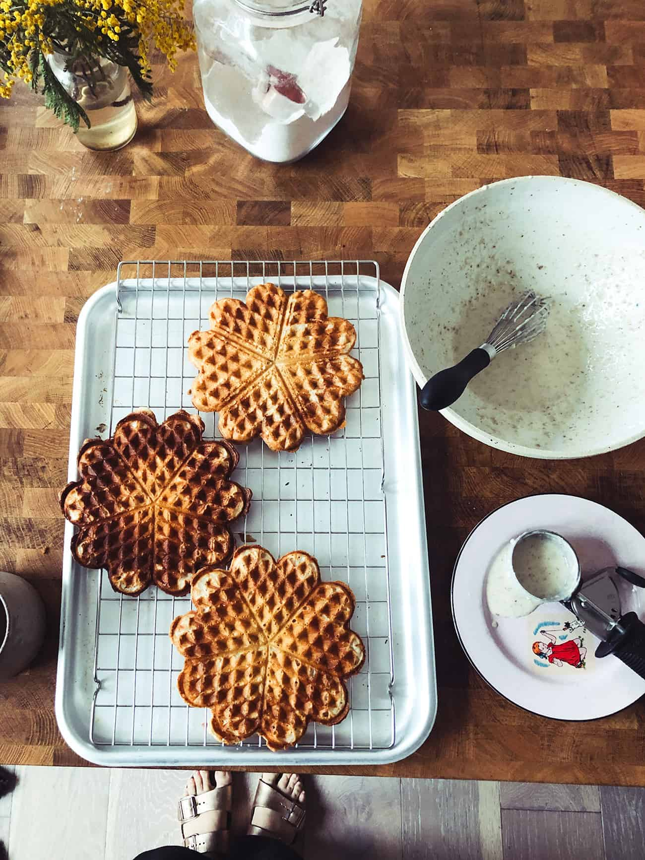a tray of vegan waffles and a bowl of waffle batter on a counter top