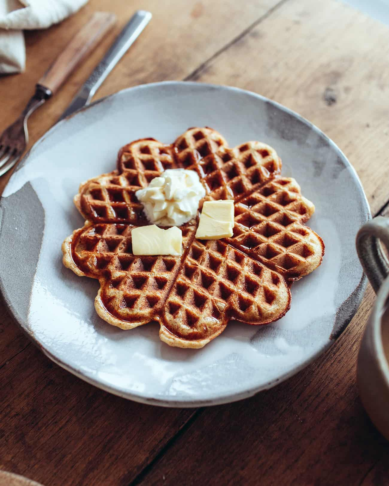 a plate with a crispy vegan waffle topped with soy cream and vegan butter
