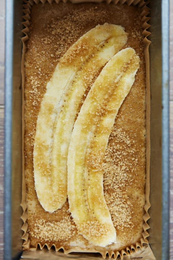 unbaked sourdough banana bread batter topped with slices of fresh banana
