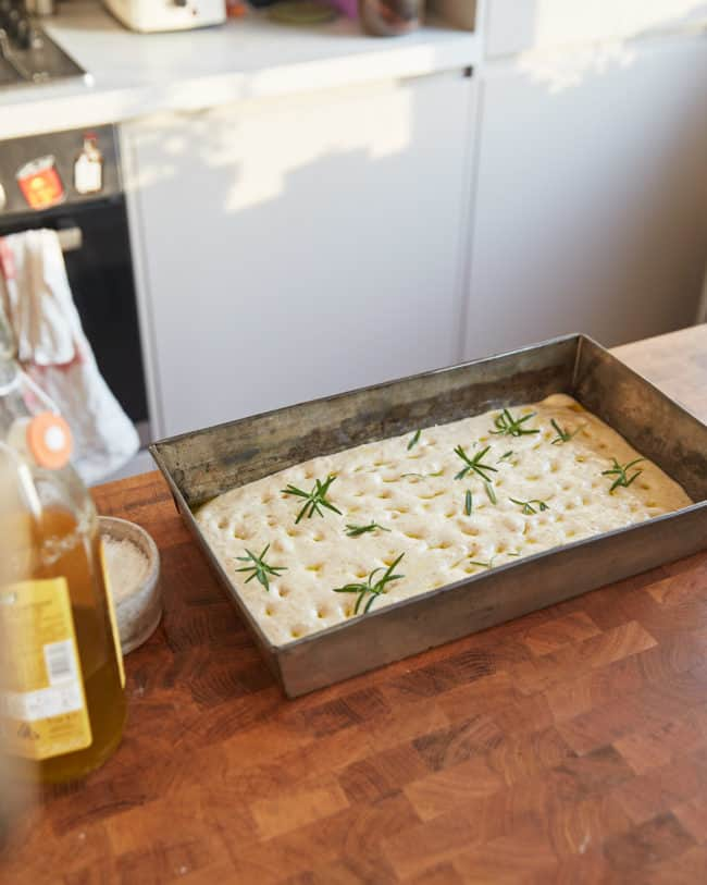 sourdough focaccia dough in a baking tray on a counter