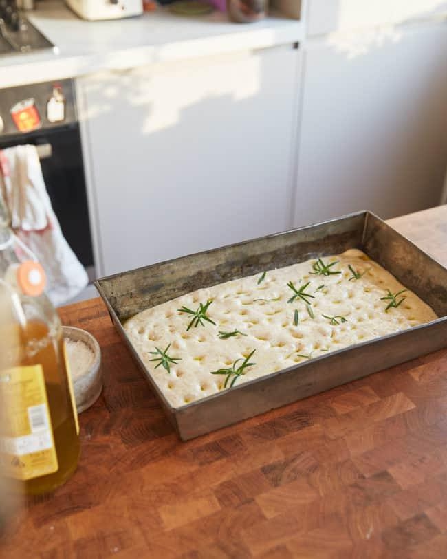 sourdough focaccia dough in a baking tray on a counter
