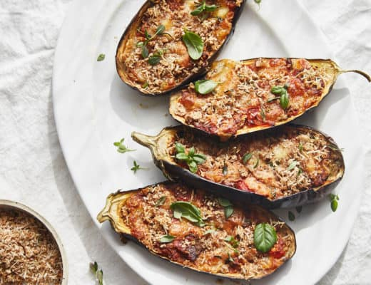a plate of stuffed aubergine halves with tomato, mozzarella and basil