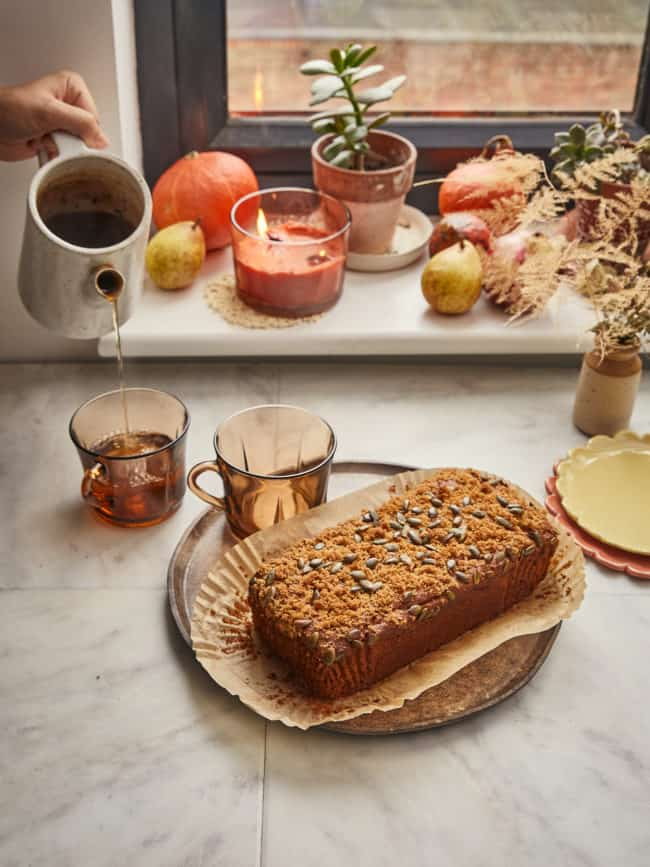 a loaf of vegan sourdough pumpkin bread with tea being poured and winter squash