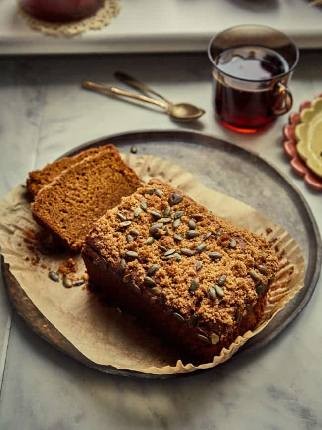 a sliced sourdough pumpkin loaf on a plate with a cup of tea