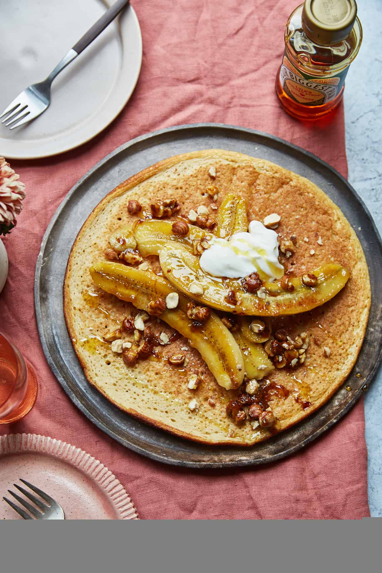 a sharing pancake topped with caramelised bananas and hazelnuts