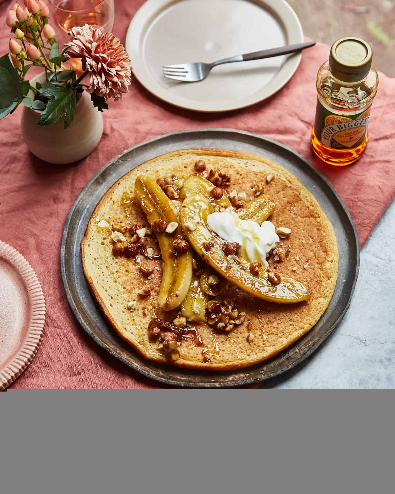 a large sharing pancake topped with caramelised bananas and yoghurt on a table setting with flowers