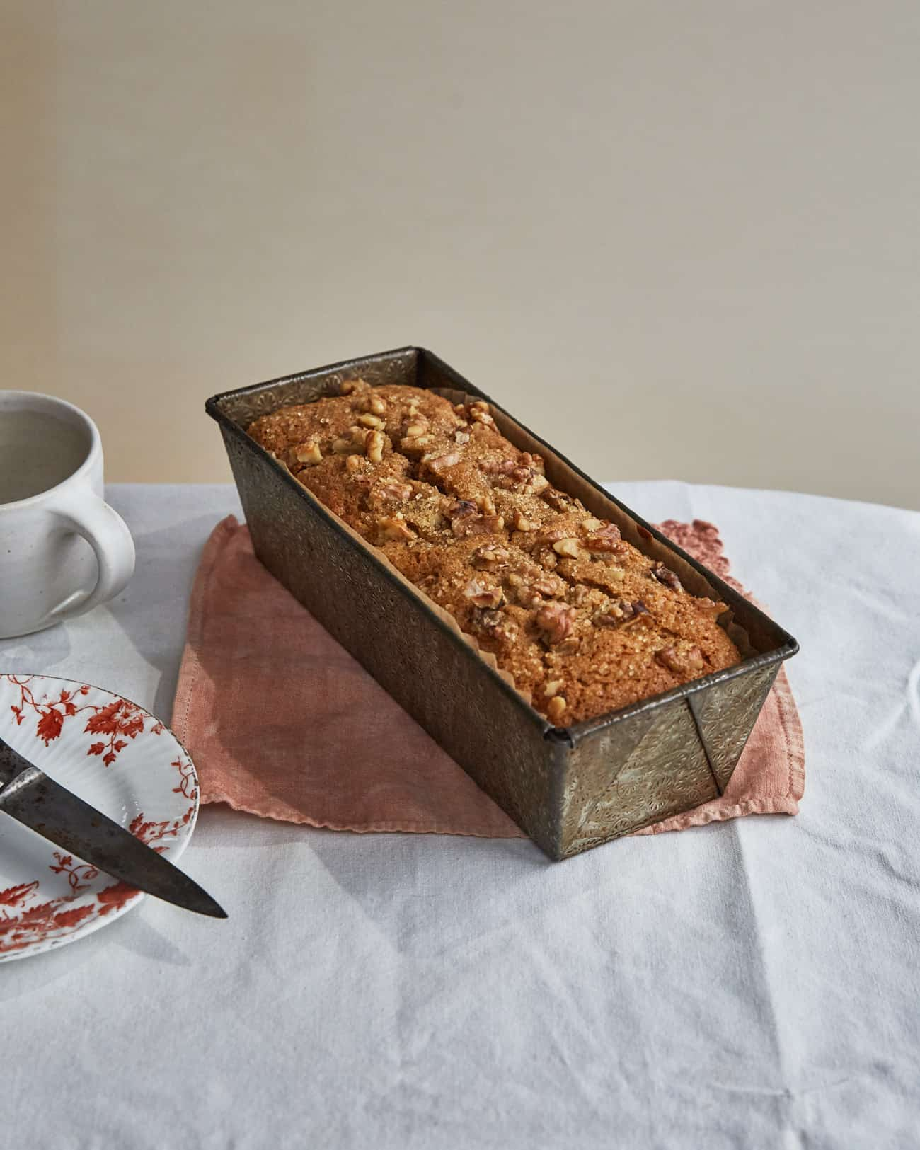 eggless banana bread in loaf tin with plate and mug